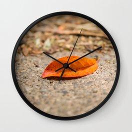 Orange leaf lying on the street Wall Clock