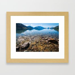Snow-capped mountains view in summer from the rocky shore of lake Wakatipu. Framed Art Print