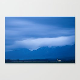 In the shadow of a mighty mountain range Canvas Print