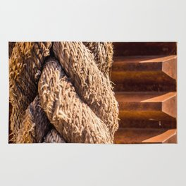 Thick braided rope from a boat, tied to a cogwheel Rug