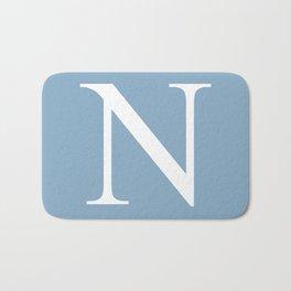 Letter N sign on placid blue background Bath Mat