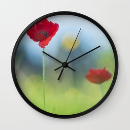 Two red poppies in a field of grass Wall Clock