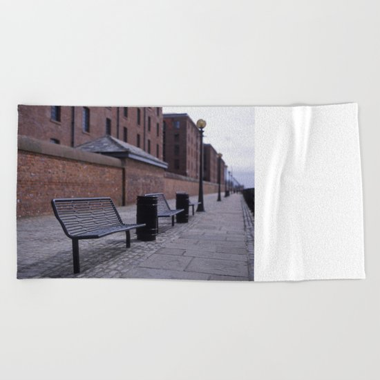 a row of benches Beach Towel
