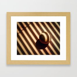 wooden ball covered with the shadow of  sunblinds Framed Art Print