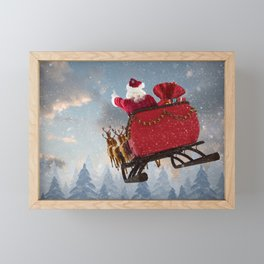 Santa Claus ride on reindeer sleigh with christmas gifts against snow falling on fir tree forest Framed Mini Art Print
