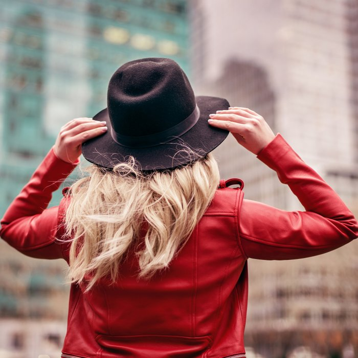 A young woman wearing a hat is walking in the streets of New York City Comforters