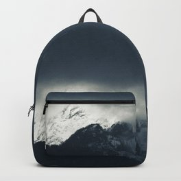 Darkness and light on snow covered mountains Backpack