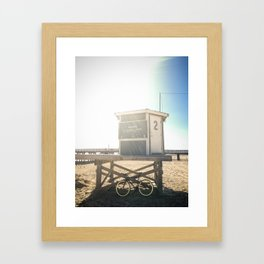 Bike leaning against lifeguard hut on beach Framed Art Print