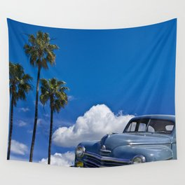 Vintage Blue Plymouth Automobile against Palm Trees and Cloudy Blue Sky Wall Tapestry