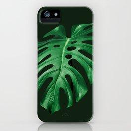 Vivid green monstera leaf on dark background iPhone Case