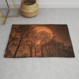 Red moon at night in the forest Rug
