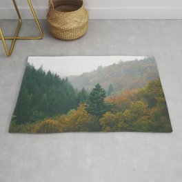 Foggy autumn forest layers disappearing in fog Rug