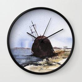 Wreckage on seashore Wall Clock