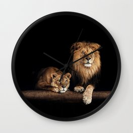 Cute lion and lioness - happy big cat family lie on the wooden log. Beautiful animals photo on dark background Wall Clock