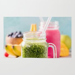 Close-up of green fresh smoothie with fruits, berries, oats and seeds, selective focus Rug