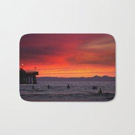 Surfers watching Sunset Bath Mat