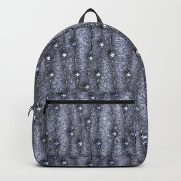 Metallic threads with beads on gray grungy background. Backpack