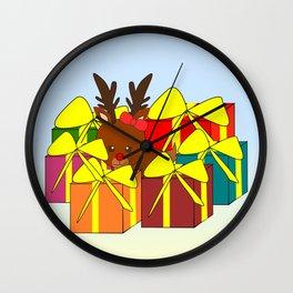 Cute reindeer hiding behind Christmas gifts Wall Clock