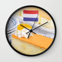 Orange tompouce, traditional Dutch pastry, on a rustic table Wall Clock