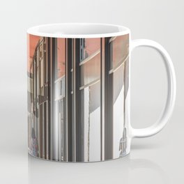 A woman from behind pushes a stroller under the arcades of the city Coffee Mug