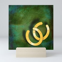 Lucky horseshoes on a textured green background Mini Art Print