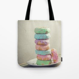 A stack of donuts on wooden table against the wall Tote Bag
