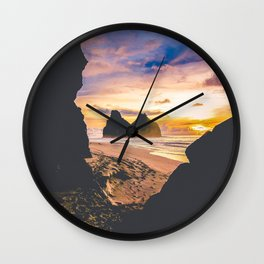 sunset and ocean through the rocks Wall Clock