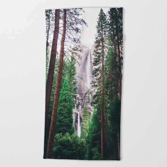 Waterfall amongst trees Beach Towel
