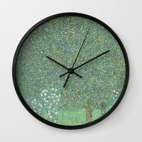 gustav klimt Wall Clocks featuring Rosebushes under the Trees - Gustav Klimt by ArtMasters