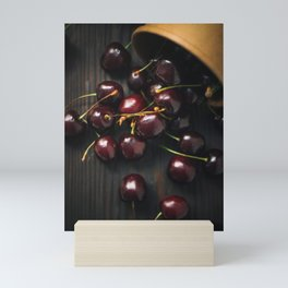 Scattered cherry from cup on black background. Mini Art Print