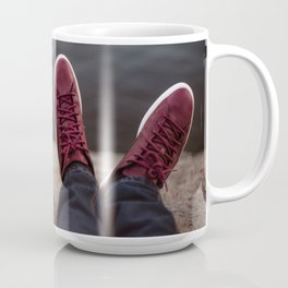 Feets with shoes of the couple on romantic date sitting on the rocks near lake Mug
