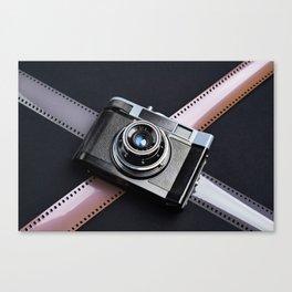 Vintage camera and films on black Canvas Print