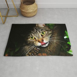 Cat licking nose hunting prey extending claws sitting on tree predator cat Rug