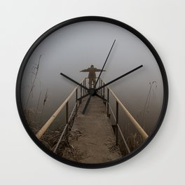 Man with open arms on a frozen pier shrouded in mist Wall Clock