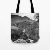 cassia beck Tote Bags featuring Cinnerdale Beck above Crummock Water with Whiteless Pike beyond. Lake District, UK. by liamgrantfoto