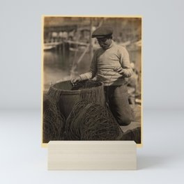 Doris Ulmann  (1882–1934), Man with mustache and hat, kneeling beside barrel with lines running into Mini Art Print
