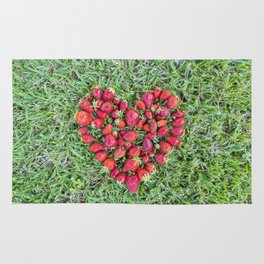 Heart made of strawberries with grass in the background Rug