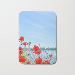 Red poppies in the lakeshore Bath Mat