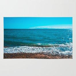 Blue sea at Greece with stony beach Rug