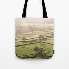 Hazy light at sunset over a valley of fields. Derbyshire, UK. Tote Bag
