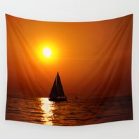 sailboat Wall Tapestries featuring A sailboat at sunset by DistinctyDesign