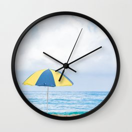 Beach umbrella in beautiful scenery with sand, blue sea and cloudy sky in Trindade, Paraty, Brazil. Wall Clock