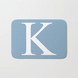 Letter K sign on placid blue background Bath Mat