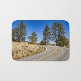 Empty Highway Road Cutting through Pine Trees and Golden Meadow in Lake Cuyamaca Bath Mat