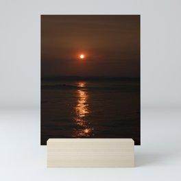 Sun setting over the sea Mini Art Print
