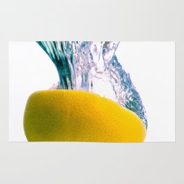 Grapefruit falls into water with big splash on white background Rug