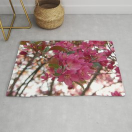 red crabapple flowers and sunset bokeh Rug