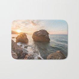 Rocky beach at sunset Bath Mat