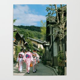 Three Women in Traditional Robes Walking through a Japanese Village Poster