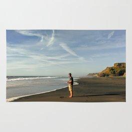 boy on black sand beach in new zealand Rug